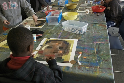 Students glue squares of color on paper to represent faces